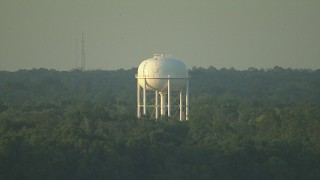 AF0001_000441 - HD stock footage aerial video of a water tower above the trees at sunset, Gulf Coast, Alabama