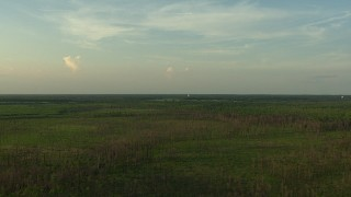 AF0001_000442 - HD stock footage aerial video of a water tower across a rural landscape at sunset in the Gulf Coast, Alabama
