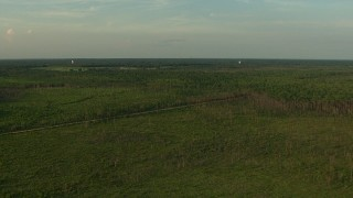 AF0001_000443 - HD stock footage aerial video of water towers and a dirt road through rural landscape at sunset, Gulf Coast, Alabama