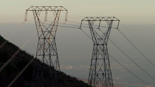 AF0001_000482 - HD stock footage aerial video zoom in and track three power line towers in the San Gabriel Mountains, California