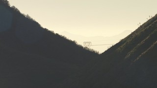 AF0001_000484 - HD stock footage aerial video of power line towers on a mountain ridge in the San Gabriel Mountains, California, sunset