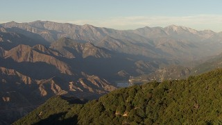 AF0001_000498 - HD stock footage aerial video approach power lines on a mountain ridge and tilt to a tower at sunset, San Gabriel Mountains, California