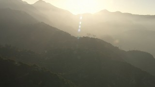 AF0001_000502 - HD stock footage aerial video of passing rows of power lines through the San Gabriel Mountains, California, sunset