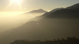 AF0001_000505 - HD stock footage aerial video of flying by hazy San Gabriel Mountains, California, sunset
