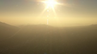 AF0001_000513 - HD stock footage aerial video sun over Verdugo Mountains and homes in La Crescenta-Montrose, California, sunset