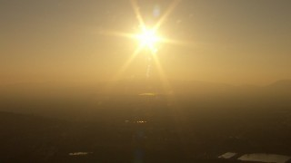 AF0001_000519 - HD stock footage aerial video of setting sun over distant hills in San Fernando Valley, California, sunset