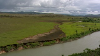 AF0001_000524 - HD stock footage aerial video of a narrow river and wide green savanna, Southern Venezuela