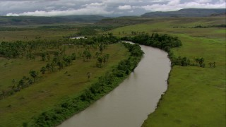 AF0001_000528 - HD stock footage aerial video of a river running through savanna past palm trees, Southern Venezuela