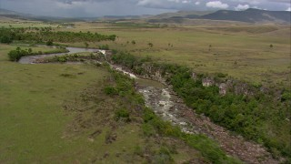 AF0001_000531 - HD stock footage aerial video flyby and away from river waterfalls in green savanna in Southern Venezuela