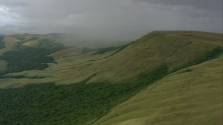 AF0001_000555 - HD stock footage aerial video of rain on a green mountain and tilt down to jungle in Southern Venezuela