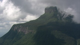 AF0001_000571 - HD stock footage aerial video zoom to a wider view of a Guiana Highlands peak covered with jungle trees in Southern Venezuela