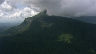 AF0001_000572 - HD stock footage aerial video of low clouds over jungle-covered mountain peak in Southern Venezuela