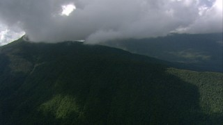 AF0001_000573 - HD stock footage aerial video of dense clouds over a jungle-covered mountain peak in Southern Venezuela