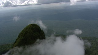 AF0001_000580 - HD stock footage aerial video orbit a green mountain peak and low clouds in Southern Venezuela