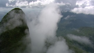 AF0001_000583 - HD stock footage aerial video orbit a green mountain peak shrouded in misty clouds in Southern Venezuela
