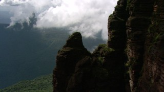 AF0001_000594 - Aerial stock footage of Flyby a steep mountain slope to approach jungle and low clouds in Southern Venezuela