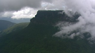 AF0001_000596 - HD stock footage aerial video zoom to a wide view of misty clouds over steep cliffs with jungle vegetation in Southern Venezuela