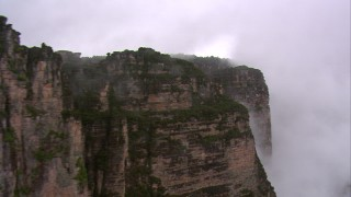 AF0001_000600 - HD stock footage aerial video flyby steep mountain cliffs in the rain in Southern Venezuela