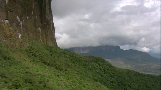 AF0001_000604 - HD stock footage aerial video fly over jungle vegetation and pan to reveal distant peaks in Southern Venezuela