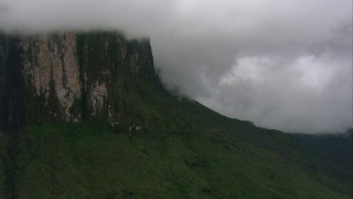 AF0001_000613 - HD stock footage aerial video zoom to a wider view of steep mountain cliffs and jungle in Southern Venezuela
