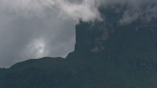 AF0001_000615 - HD stock footage aerial video zoom to a wider view of steep mountain cliffs and jungle with low clouds Southern Venezuela