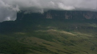 AF0001_000616 - HD stock footage aerial video zoom in on steep mountain slopes and jungle beneath clouds in Southern Venezuela