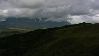 AF0001_000623 - HD stock footage aerial video of a mountain across savanna seen from jungle on a green slope in Southern Venezuela