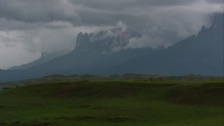 AF0001_000628 - HD stock footage aerial video zoom to a wider view of cloud-shrouded peaks seen from hilly savanna in Southern Venezuela