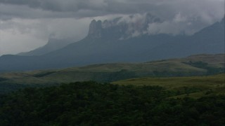 AF0001_000631 - HD stock footage aerial video of cloud-topped mountains seen from green hills in Southern Venezuela