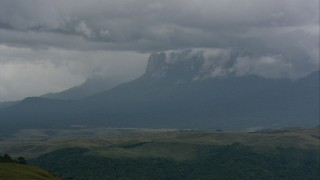 AF0001_000633 - HD stock footage aerial video zoom in on the cloud-capped mountains beyond green hills in Southern Venezuela