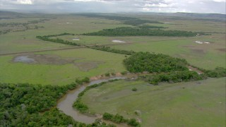 AF0001_000664 - HD stock footage aerial video follow a river to approach a country highway and bridge in Southern Venezuela