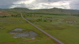 AF0001_000669 - HD stock footage aerial video of following country highway past rural houses on the savanna, Southern Venezuela