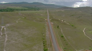 AF0001_000673 - HD stock footage aerial video fly over a river bridge and power lines to track a black car on the country highway in Southern Venezuela