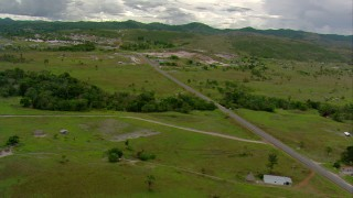 AF0001_000675 - HD stock footage aerial video of rural homes and farms by a country highway near a small town in Southern Venezuela
