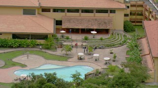 AF0001_000688 - HD stock footage aerial video zoom in to a closer view of a small town hotel with a pool in Southern Venezuela