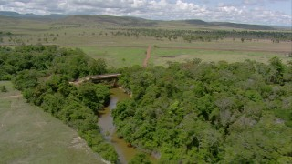 AF0001_000693 - HD stock footage aerial video fly over a river and bridge in the trees, and follow dirt road to country highway, Southern Venezuela
