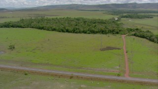 AF0001_000694 - HD stock footage aerial video of a country highway through the savanna in Southern Venezuela
