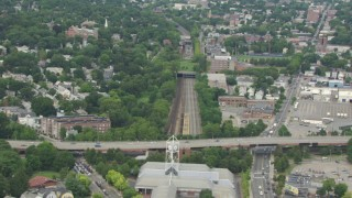 AF0001_000708 - HD stock footage aerial video fly over Forest Hills Station, and tilt to reveal homes and Downtown Boston skyline, Massachusetts