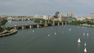 AF0001_000784 - HD stock footage aerial video fly over sailboats to approach the Longfellow Bridge as a commuter train crossing, Boston, Massachusetts