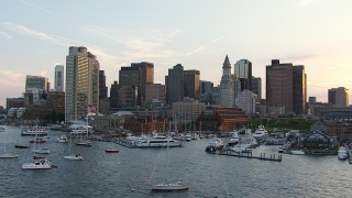 AF0001_000788 - HD stock footage aerial video flyby boats in the marina and skyscrapers in Downtown Boston, Massachusetts, sunset