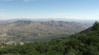 AF0001_000868 - HD stock footage aerial video fly over the Little Rincon Mountains to reveal Mae West Peaks, Arizona