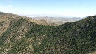 AF0001_000870 - HD stock footage aerial video fly over Mae West Peaks to reveal a desert valley near Dragoon, Arizona