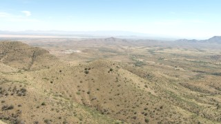 AF0001_000872 - HD stock footage aerial video fly over Mae West Peaks to approach a quarry near Dragoon, Arizona
