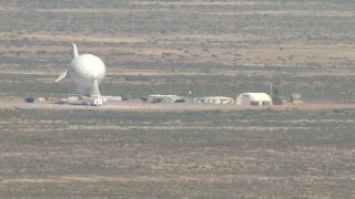 AF0001_000880 - Aerial stock footage of Flying by a blimp at a small airfield, Arizona Desert