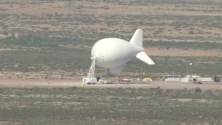 AF0001_000884 - Aerial stock footage of A small white blimp at a desert airfield, Arizona