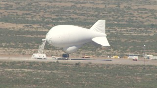 AF0001_000885 - HD stock footage aerial video flyby a small blimp at an airfield in the Arizona Desert