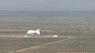 AF0001_000886 - Aerial stock footage of A white blimp at an airfield in the middle of the Arizona Desert