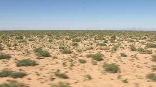 AF0001_000905 - Aerial stock footage of Passing desert vegetation on a wide desert plain in New Mexico
