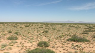 AF0001_000907 - HD stock footage aerial video pan across a wide desert plain in New Mexico