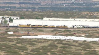 AF0001_000918 - HD stock footage aerial video of a train passing a warehouse in El Paso, Texas